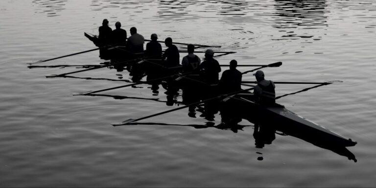 Kuvituskuva viestintätoimisto Ahjon blogiin, jonka aiheena on Nordic Business Forum. Mustavalkoisessa kuvassa on pitkä soutuvene, jossa istuu yhdeksän soutajaa. Vene on keskellä tyyntä vettä.