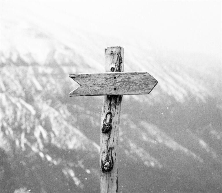 kuvituskuva, jossa on puusta tehty kyltti, joka on muodoltaan nuoli ja osoittaa oikealle, taustalla on luminen vuorimaisema