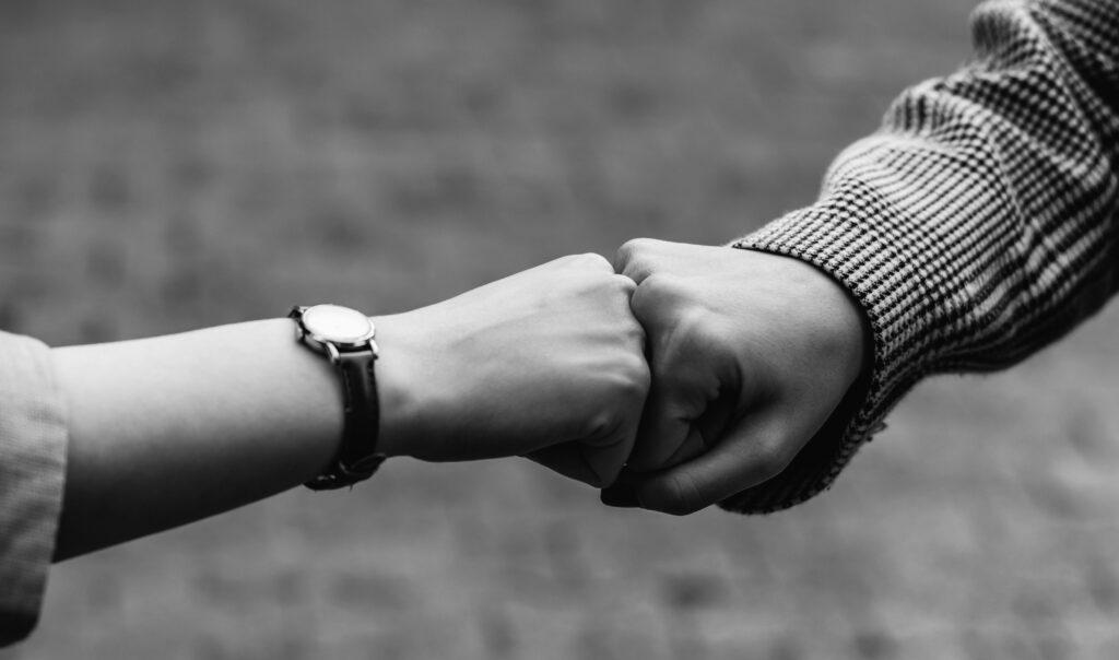 kahden ihmisen kädet antamassa toisilleen fistbumpin